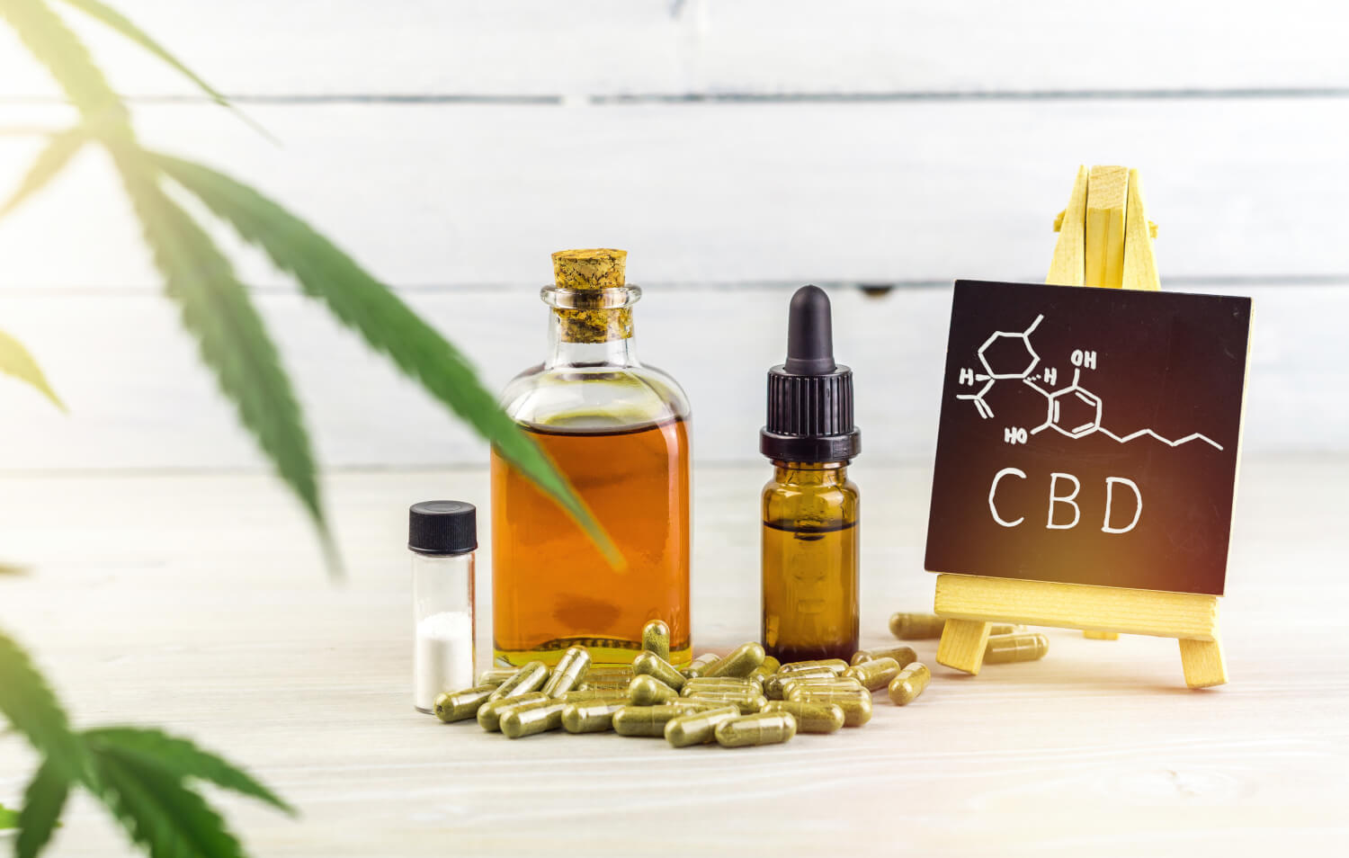 Cannabidiol CBD oils, capsules and crystals isolate with small blackboard with CBD word and chemical structure